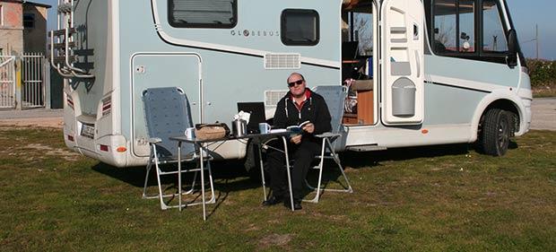 Peter Budig sitzt in Sonne vor Camper