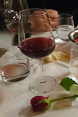 Tisch mit Rotwein und Rose