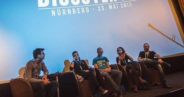 Moderator und vier Podiumsteilnehmer auf Bühne im Cinecitta Nürnberg
