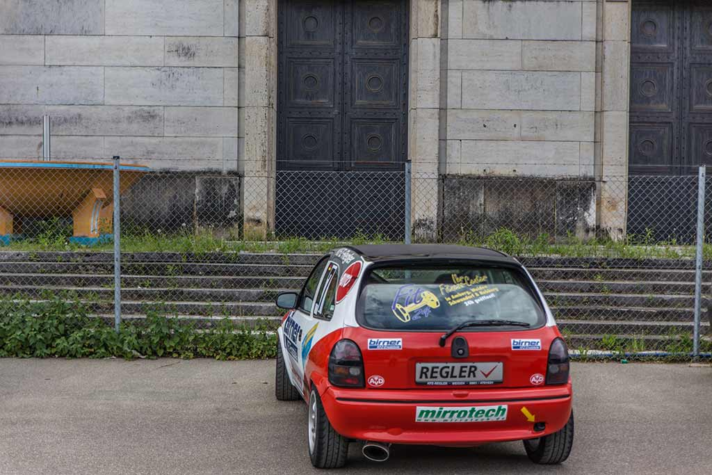 rot weißer Opel Corsa Rennwagen vor Mauer Rückseite Steintribüne