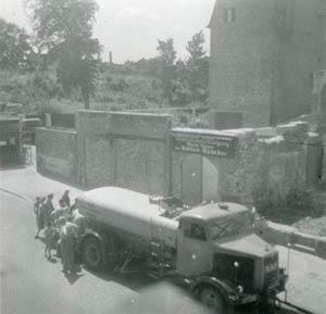 1950 standen von Kadeders Firmengebäude nur noch Ruinen. Eine Traube von Menschen schart sich um einen Tanklastzug, der wohl frisches Trinkwasser verteilt.
