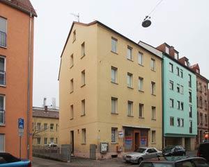 Das Haus Adamstraße 15, ein typisches Beispiel für eine kriegsbedingt vereinfachte und verputzte Altbaufassade.