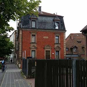 Die südliche Schmalseite der Schweinauer Hauptstraße 71 mit Portal und Inschrifttafel.