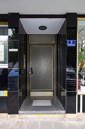Stahlrahmentür mit eloxierten Rahmenleisten und Reliefglas, schräg montierter Türgriff und noble Fliesenzier – der Eingang der Bleichstraße 2.