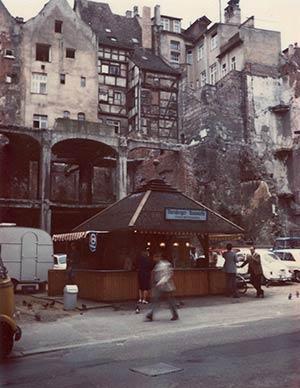 1965 standen nur noch Teile des Eisenbetongerüsts der Kaiserstraße 15 aufrecht. Davor mampften die Passanten Drei im Weggla.