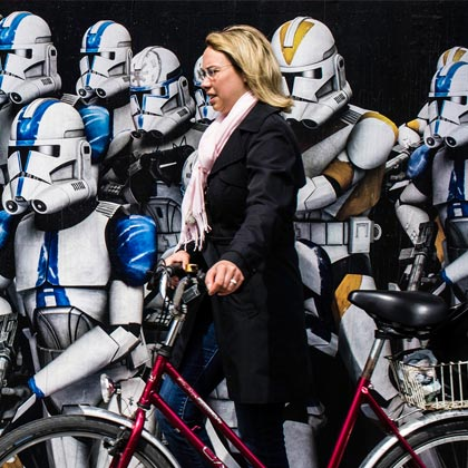 Frau mit Fahrrad vor Robotern